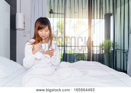 Young woman woke up and drinking coffee or tea on bed under sunlight. Good morning.