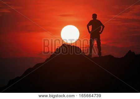 Silhouette of young man standing on the top of the mountain with beautiful sunset background concept for success and victory.