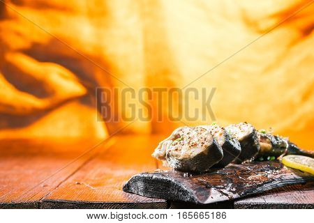 Salmon steaks on rustic board over fire light background