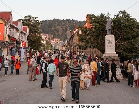 SHIMLA, INDIA. June 8, 2009: British style shops and buildings in Shimla, people on the Mall Road in the evening. Mall Road, Shimla, Himachal Pradesh, India