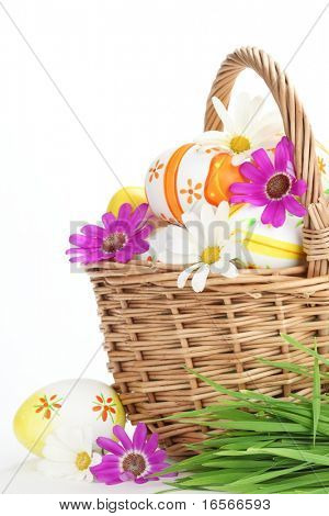 Basket full of easter eggs and spring flower.