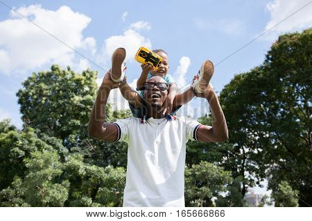 African American Father And Son Piggyback In Outdoor Park