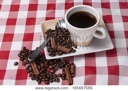 Cup of coffee and coffee beans on a small plate.