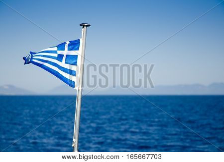Close-up of Greece flag waving on metal flagpole over vessel with blue sea sky and mountainous horizon in background