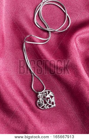 Silver heart shaped medallion on pink satin