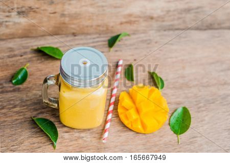 Juicy Smoothie From Mango In Glass Mason Jar With Striped Red Straw On Old Wooden Background. Health