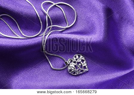 Silver heart shaped medallion on purple crumpled satin