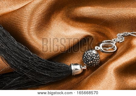 Black silk tassel pendant on crumpled golden satin closeup
