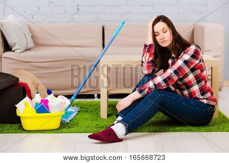 Tired young woman sitting on the floor, being at home, after cleaning the apartment. Next to her is a mop and a bucket with detergent.
