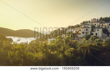 View of resort town houses on hill near sea with lots of green foliage and boats on water in distance - Sivota Greece
