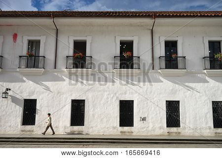 September 1, 2016 Popayan, Colombia: a woman walks in the front of a white colonial building in the afternoon sun