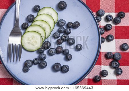 Cucumbers and blueberries on plate with a fork.