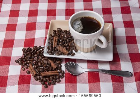 Beans and cinnamon by cup of coffee.