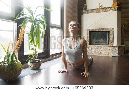 Young attractive smiling woman practicing yoga, fitness, stretching in upward facing dog exercise, Urdhva mukha shvanasana pose, working out, wearing sportswear, grey pants, bra, indoor, home interior