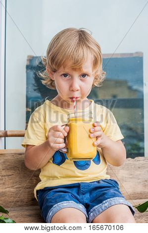 Boy Drinking Juicy Smoothie From Mango In Glass Mason Jar With Striped Red Straw On Old Wooden Backg