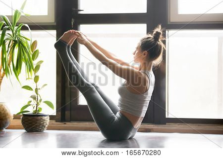Young attractive woman practicing yoga, sitting in Both big toe exercise, Paripurna Navasana pose, working out, wearing sportswear, grey pants, bra, indoor full length, home interior background