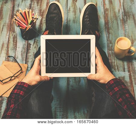 Man holding tablet with copy space while sitting at the wooden floor top view