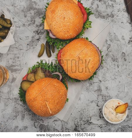 Three burger with fries on a white surface top view