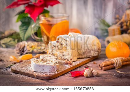 Christmas cake, slices of stollen with raisins on rustic wooden background with tangerines and a cup of hot tea. Traditional festive dessert