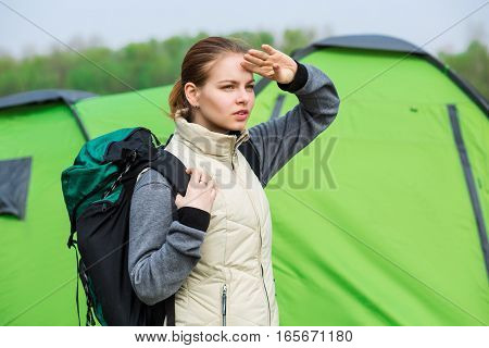 Woman backpacker with a backpack looks into the distance, against the background of tourist tents, hiking, active lifestyle