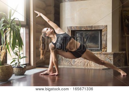 Young attractive woman practicing yoga, standing in Extended Side Angle exercise, Utthita parsvakonasana pose, working out, wearing sportswear, black tank top, shorts, indoor full length, home