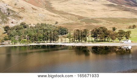 Buttermere lake reflections, trees building and fell side