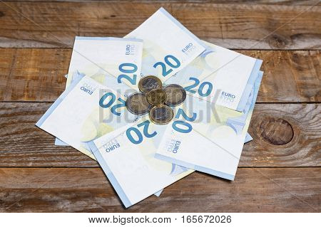 Euro banknotes and coins on an old wood