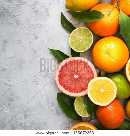 Different citrus fruit on grey concrete table. Whole and sliced fruit. Food background. Healthy eating and diet.