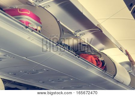 Airplane interior with overhead luggage compartment. doors opened before take-off.