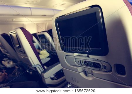 Economy class airplane interior. LCD displays on the rear side of seats.