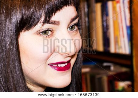 Portrait of a smiling beautiful girl with red lips on the background of bookshelves.