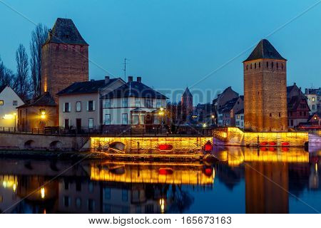 Medieval stone tower on the waterfront at night in Strasbourg. Alsace. France.