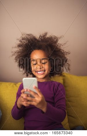 Young little girl texting on her mobile phone indoors. Feeling happy.