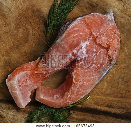 salmon steak trout frozen semi thawed with sprigs of greenery on a wooden background