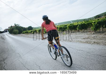 Young woman on a bicycle on a road between vineyards.