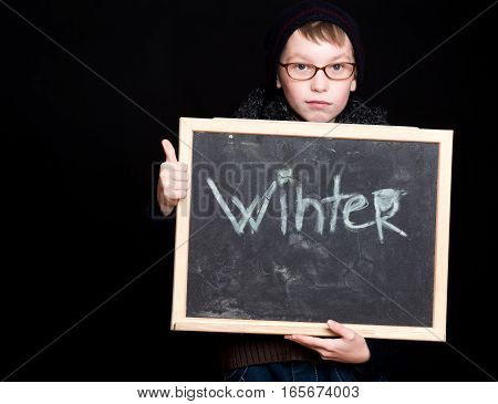 small boy or cute nerd kid in glasses hat and fashionable knitted scarf on black background holds blackboard with winter text in frame