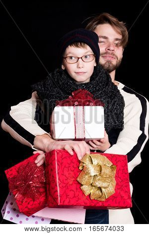 small smiling boy or cute nerd kid in glasses hat and fashionable knitted scarf and handsome man or bearded guy on black background holds white present boxes with red bow