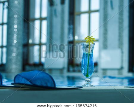 Blue cocktail drink in glass with yellow palm stick and slippers at swimming pool with water indoors on blurred background