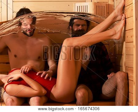 Handsome men bathers and sexy female body with slim legs wet with big splash of water in sauna thermal bath on wooden background
