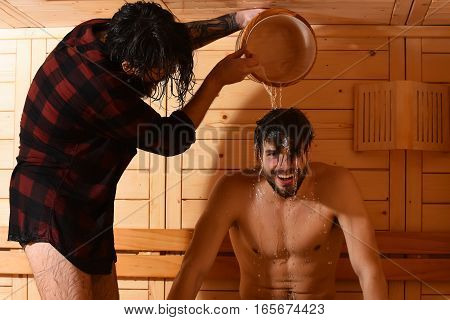 Handsome man in red checkered shirt pours water from bucket on head of cheerful young male bather with muscular torso in sauna thermal bath on wooden background