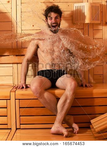 Excited man or bather with muscular sexy torso body wet with big splash of water in sauna thermal bath on wooden background