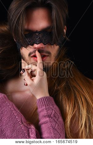 blonde girl in pink knitted sweater wore lace bandage on eyes of her guy with raised finger with stylish hair and naked chest in studio on black background