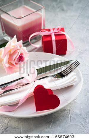 Valentines day table setting. Plate silverware flower and gift box. Top view copy space.