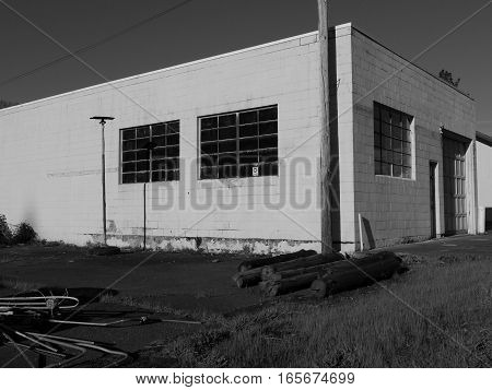 An old abandoned concrete block building with multiple window panes and electrical equipment stacked outside on a sunny spring day in the little town of Oakridge in Lane County in Western Oregon.