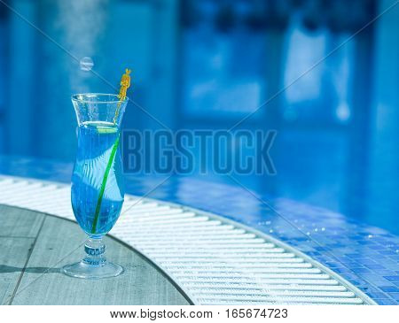 Blue cocktail drink in glass with yellow palm stick on ceramic tile at mosaic swimming pool with water indoors on blurred background