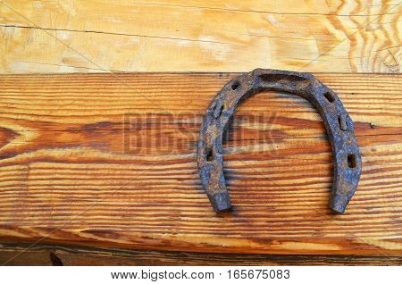old horseshoe hanging on wooden wall. It brings happiness abundance and prosperity in the family. space for text