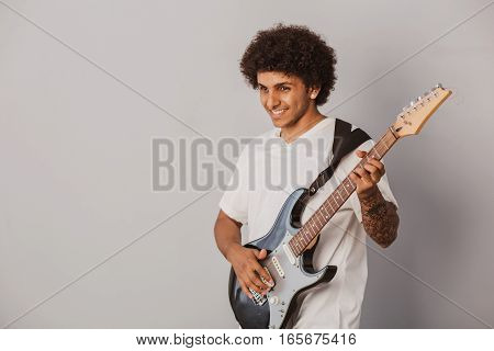 Positive curly haired man, expressive plays the bass guitar, on gray background. Cheerful musician.
