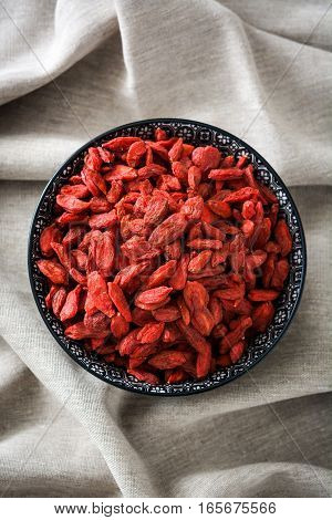 Wolfberries or Goji berries in bowl on tablecloth.Top view