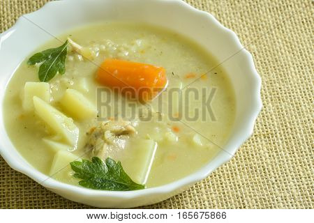 Barley soup in a white bowl on linen background