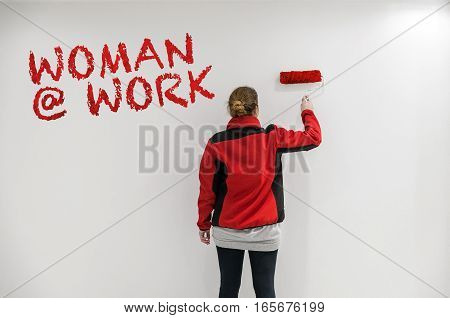 Female Painter With Red Paint Roller In Front Of Wall As Template